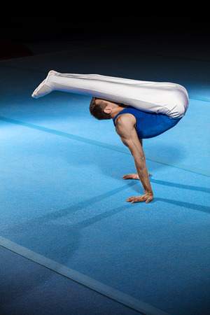 boy gymnast: portrait of young man gymnasts competing in the stadium