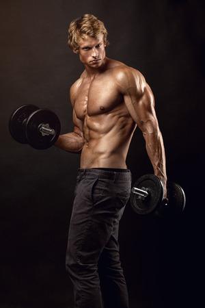 Gespierde bodybuilder man doet oefeningen met halters op een zwarte achtergrond