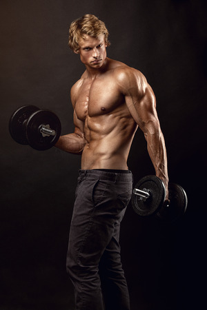Muscular bodybuilder guy doing exercises with dumbbells over black background