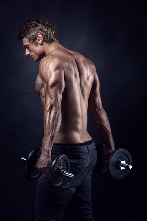 Musclé bodybuilder gars faire des exercices avec des haltères sur fond noir Banque d'images - 65033851