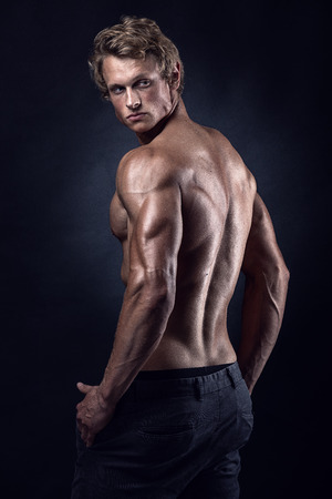 強い運動男性フィットネス モデル ポーズの背中の筋肉、上腕三頭筋、広背筋