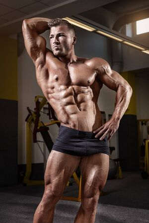 male body: Strong Athletic Man Fitness Model Torso showing muscles in yellow gym