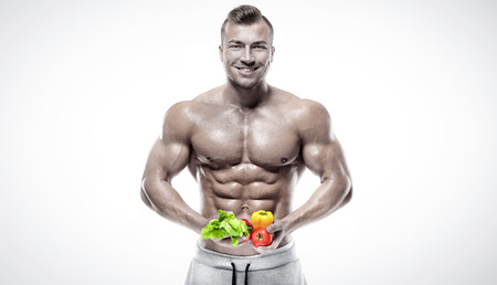 hombre comiendo: culturista en forma y saludable que sostiene un verduras frescas, abdominal en forma, aislados en fondo blanco, de color retocada Foto de archivo