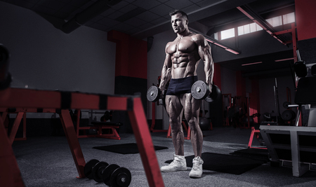 latissimus: Muscular bodybuilder guy doing exercises with dumbbells in gym Stock Photo