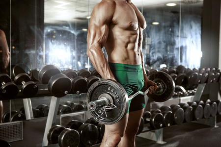 latissimus: Muscular bodybuilder guy doing exercises with big dumbbell in gym Stock Photo