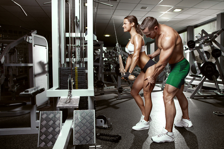beautiful young sporty sexy couple doing triceps workout in gym photo
