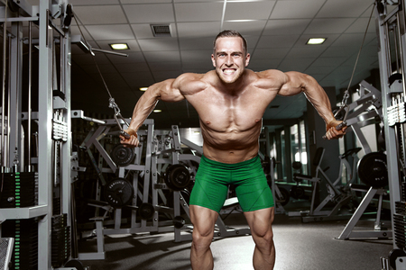 Muscular bodybuilder guy doing exercises workout in gym - breast muscles photo