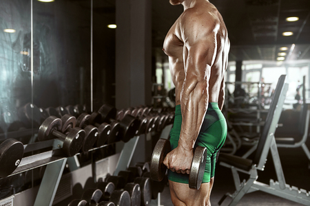 Muscular bodybuilder guy doing exercises with big dumbbell in gym photo