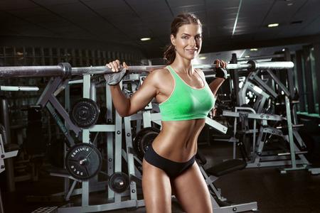 femmes nues sexy: belle femme sexy sportif faisant séance d'entraînement squat dans le gymnase Banque d'images