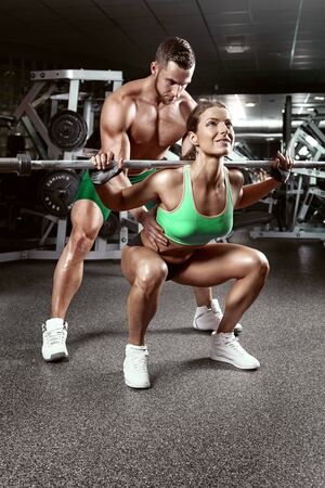 beautiful young sporty sexy couple doing squat workout in gym photo