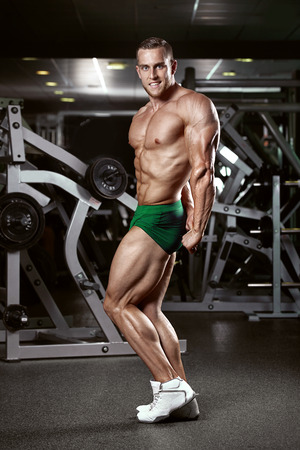 Strong Athletic Man Fitness Model Torso showing muscles in gym photo