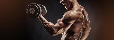 man gym: Muscular bodybuilder guy doing exercises with dumbbell over black background