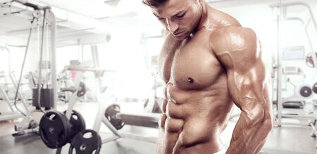 muscle guy: Muscular bodybuilder guy standing on gym and posing triceps muscle