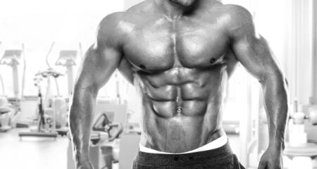 muscle guy: Muscular bodybuilder guy standing on gym and posing abdominal muscle