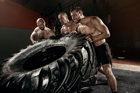 cross strongman training - three men flipping big tire 版權商用圖片