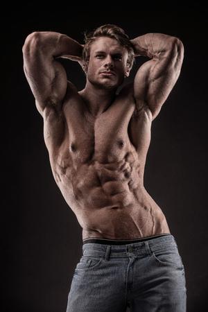 portret van sterke atletische Fitness man met grote spieren op zwarte achtergrond