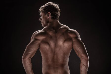 Strong Athletic Man Fitness Model posing back muscles, triceps, latissimus over black background Stock Photo