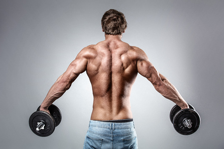 Strong Athletic Man Fitness Model posing back muscles, triceps, latissimus over grey background