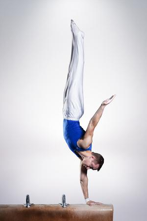 retrato de hombre joven gimnastas que compiten en el estadio