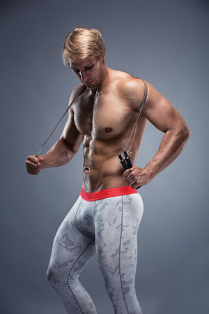 sixpack: Muscular bodybuilder guy doing exercises with jump rope over gray background