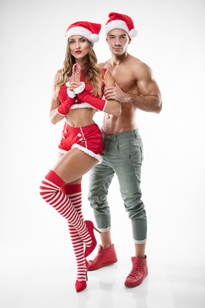beautiful couple in santa claus clothes over white background Stock Photo