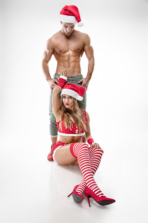 beautiful sexy couple in santa claus clothes over white background Stockfoto