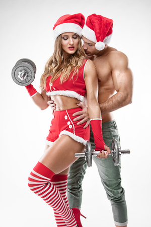 beautiful sexy couple in santa claus clothes doing workout with dumbbell over white background