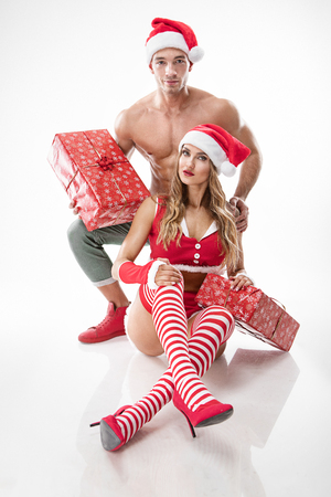 beautiful sexy couple in santa claus clothes over white background 版權商用圖片