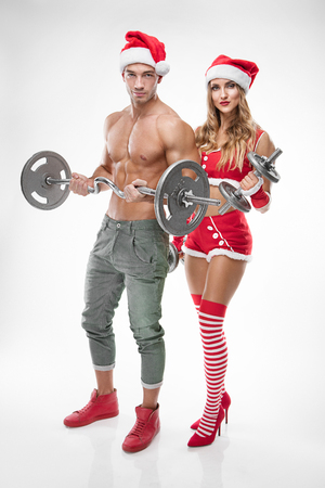beautiful couple in santa claus clothes doing workout with dumbbell over white background