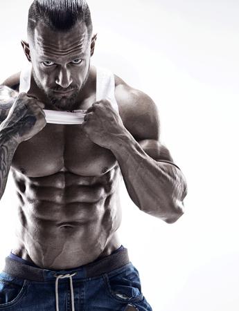 Retrato de hombre fuerte Athletic Fitness mostrando grandes músculos sobre fondo blanco.