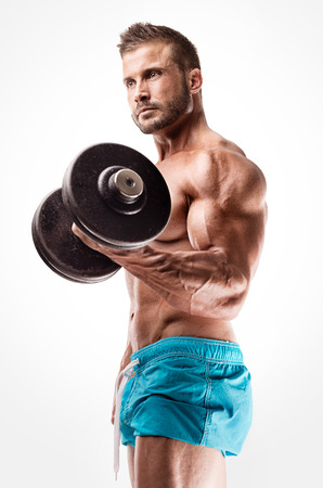 Muscular bodybuilder guy doing exercises with big dumbbells over white background
