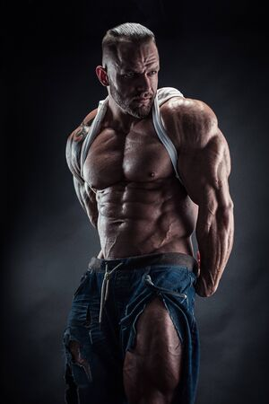 portrait of strong Athletic Fitness man showing big muscles over black background