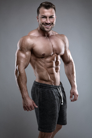 Strong Athletic Man shows body and abdominal muscles over gray background