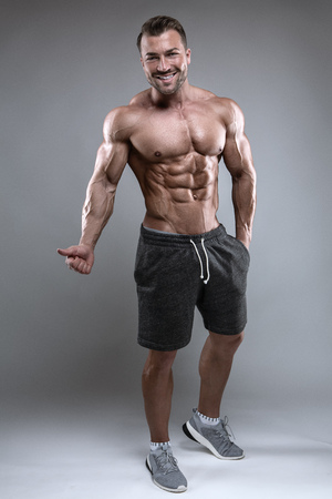 Strong Athletic Man shows body and abdominal muscles over gray background Imagens - 100024334