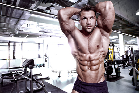 Strong Athletic Man Fitness Model Torso showing abdominal six pack in gym