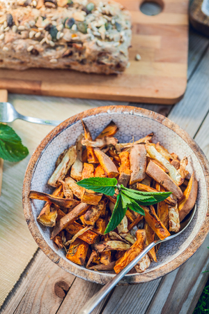 bowl of grilled sweet potatoes on a wooden garden table 版權商用圖片