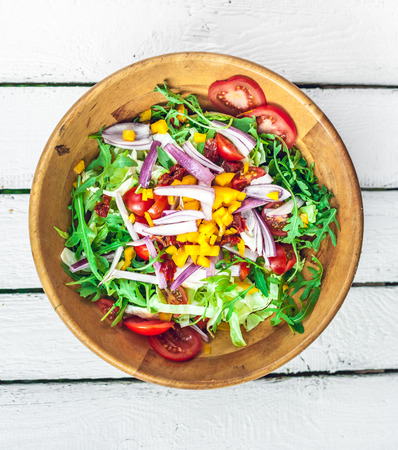 fresh colorful vegetable salad on a white wooden table