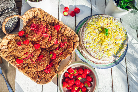 healthy homemade strawberries biscuits with carrot cake from oat flakes laid on a white garden rustic table