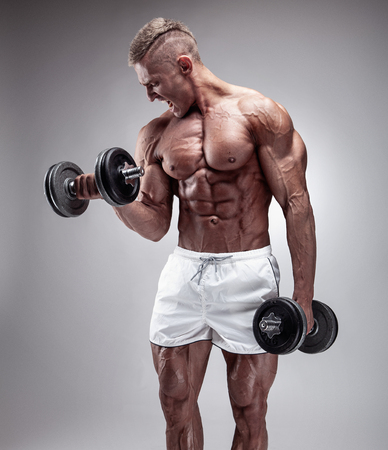 Muscular bodybuilder guy doing exercises with dumbbell over gray background Stock Photo