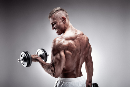 Muscular bodybuilder guy doing exercises with dumbbell over gray background Banque d'images