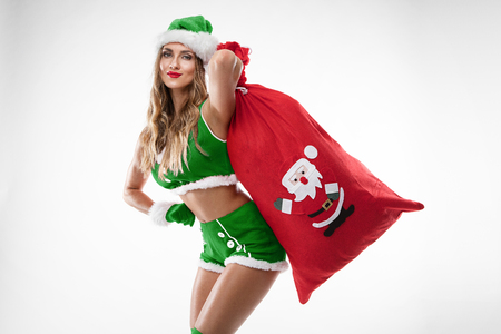 beautiful sexy girl with gifts bag wearing santa costume over white background