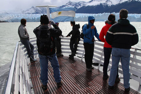 icefield: PERITO MORENO, ARGENTIN - DECEMBER 27, 2013   Group of tourists observing the Perito Moreno Glacier from a boat  The Perito Moreno Glacier is one of few glaciers that is growing and is one of the most important attractions in the Argentine Patagonia  Editorial