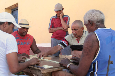 TRINIDAD, CUBA, FEBRUARY 18, 2014   Old men playing dominoes in the streets   Most domino games are blocking games, where the objective is to empty one