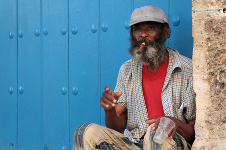 HAVANA, CUBA, FEBRUARY 15, 2014   Old man smoking cigar in the street  Cigars are a famous Cuban product worldwide and almost the whole production is exported  Editorial