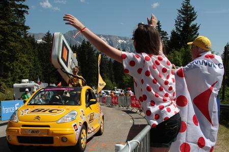 Chamrousse, Frankrijk, 18 juli 2014 Publiciteit karavaan van de Tour de France Een konvooi van voertuigen met reclame karakter, vóór het verstrijken van de lopers, verdeelt voorwerpen van allerlei aard Redactioneel