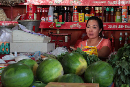 sanur: BALI, INDONESIA, AUGUST 18, 2014 : Unidentified woman sells food at the market of Sanur. The Balinese economy is largely agriculture-based in terms of both output and employment. Editorial
