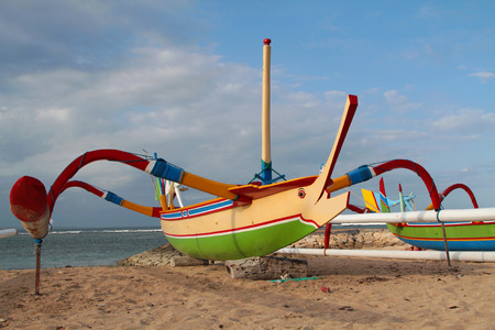 sanur: BALI, INDONESIA, AUGUST 17, 2014 : Jukung on the beach of Sanur. A jukung is a small wooden Indonesian outrigger canoe and a traditional fishing boat, highly decorated with a marlin-like prow.