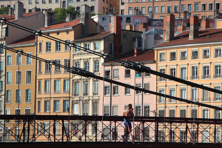 belongs: LYON, FRANCE, SEPTEMBER 7, 2014 : A runner crosses the Saone River on Saint-Vincent pedestrian bridge. The district of Quais de Saone belongs to the zone classified as a World Heritage Site by UNESCO. Editorial