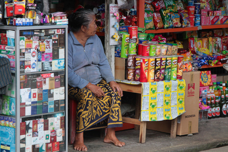 BALI, INDONESIA, AUGUST 16, 2014 : Old woman seats at the entrance of her store in Tirtagganga, a village of Bali.