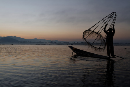 INLE LAKE, MYANMAR, December 14, 2014 : Fishermen on Inle lake in morning light. These fishermen are practicing a distinctive rowing style, wrapping a leg around the oar.